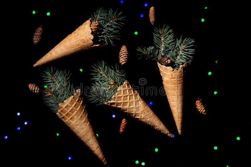 Christmas abstraction. A four waffle cones with sprigs of a Christmas tree lie on reflecting black surface, In the distance bl. Ue and gteen garlands sparkle royalty free stock image