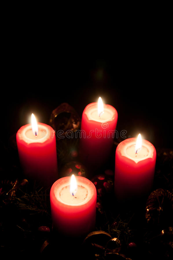 Christmas advent wreath with burning candles. Christmas advent wreath with red burning candles - black background royalty free stock photo
