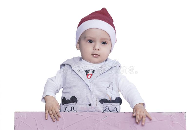 A little boy with Santa cap holding the blank paper. Santa baby boy with an empty white card. Copy space for your advertising and stock image
