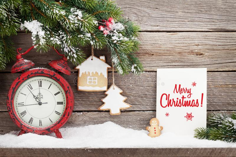 Christmas alarm clock and fir tree branch. Covered by snow in front of wooden wall. View with copy space stock photo
