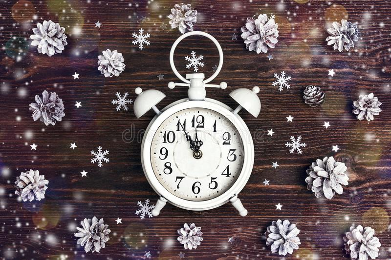 Christmas alarm clock with snow painted pine cones on wooden background. Christmas timer. stock photos