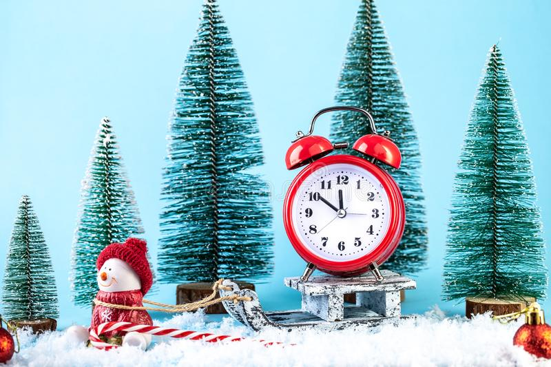 Christmas alarm clock on a wooden sled in the snow, with snowman toy royalty free stock images