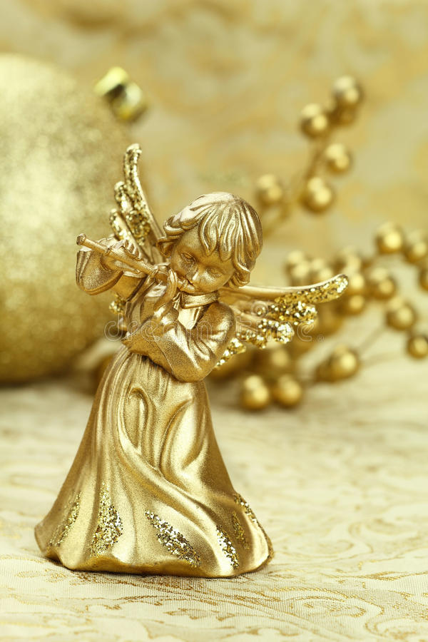 Christmas angel. Playing a flute with golden decoration at the background stock photo