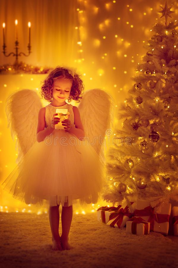 Christmas Angel Child with Wings hold Lighting Candle, Xmas Tree royalty free stock photo