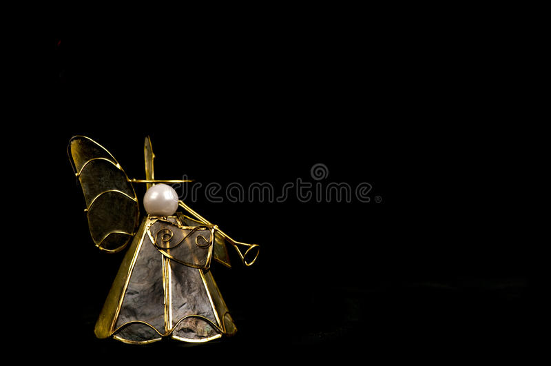 Christmas angel decoration with trumpet on black. stock image