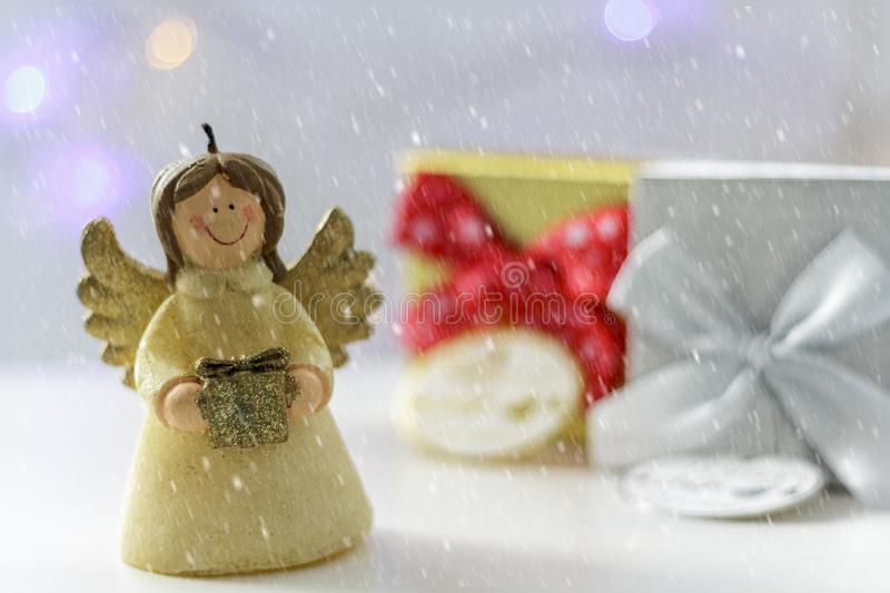 Christmas angel with gift boxes, christmas lights on the background and snow royalty free stock photo