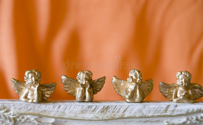 Christmas angels. Golden christmas angels on orange background stock photography