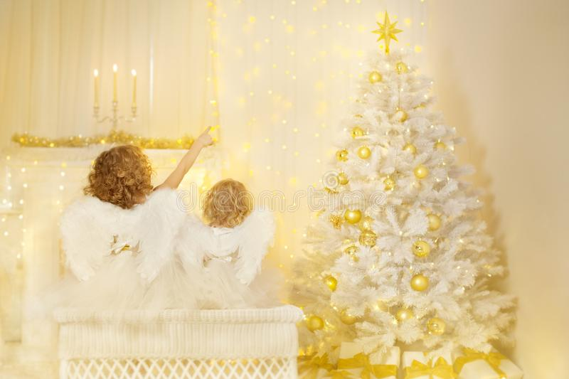 Christmas Angels looking to Xmas Tree, Children Wings on Back. Christmas Angels looking to Xmas Tree, Children with Wings Back View Pointing to Lighting Star royalty free stock image