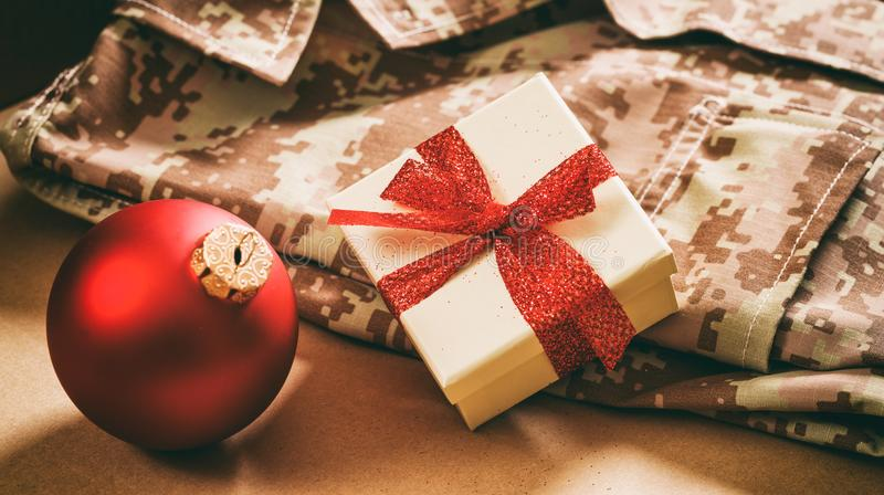Christmas in the army. Christmas ball and gift box on an American military uniform royalty free stock image