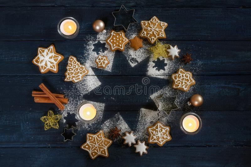 Christmas arrangement with gingerbread cookies, spices and burning candles on a star from icing sugar on a dark blue wooden. Background, copy space, high angle stock image