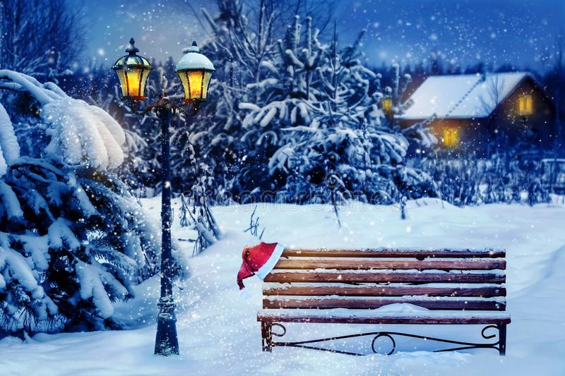 Christmas art card. Santa hat on a bench in the snow against the background of the Christmas winter forest. Village house in the b stock photos