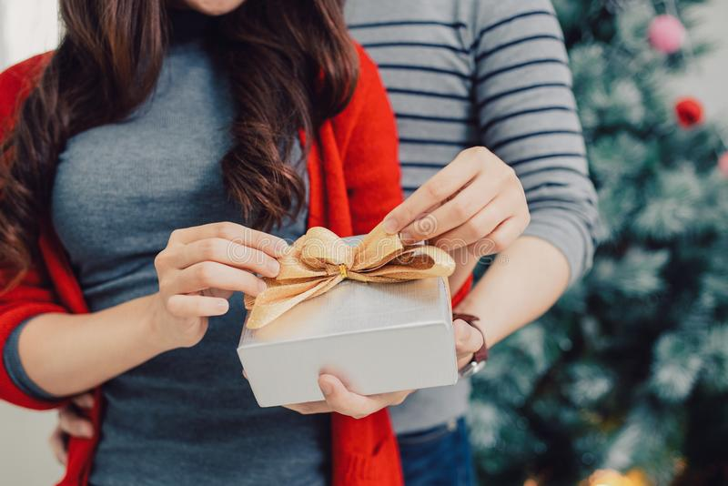 Christmas Asian Couple. A handsome man giving her girlfriend/wife a gift at home celebrating New Year People. Christmas Asian Couple. A handsome men giving her royalty free stock image