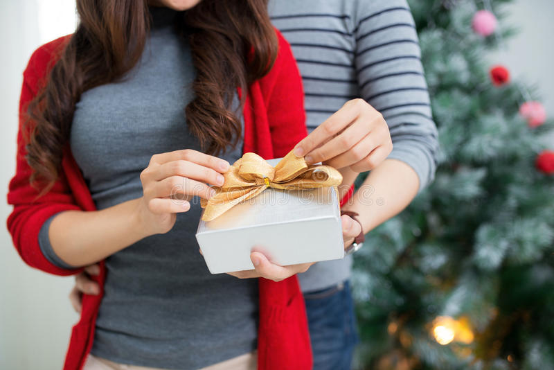 Christmas Asian Couple. A handsome man giving her girlfriend/wife a gift at home celebrating New Year People. Christmas Asian Couple. A handsome men giving her stock photography