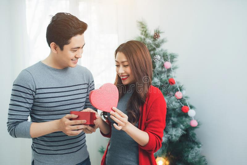 Christmas Asian Couple. A handsome man giving her girlfriend/wife a gift at home celebrating New Year People stock image