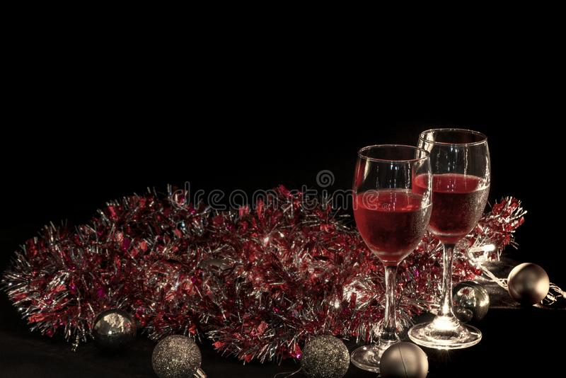 Christmas atmosphere,two red wine glass against christmas lights decoration background stock photography