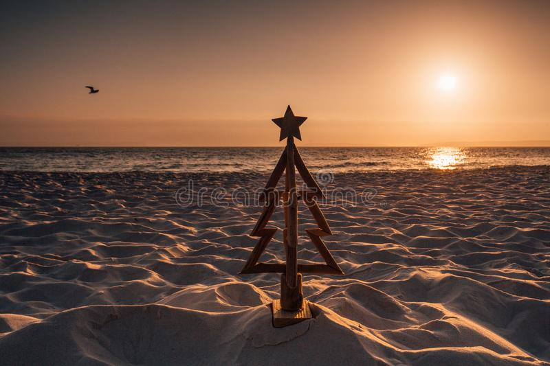 Christmas in Australia is held in the summer months and is usually spent outdoors or by the beach. A wooden Christmas tree stands royalty free stock photos