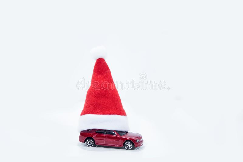 Christmas auto sale abstract photo. Red car under the New Year`s hat royalty free stock photography
