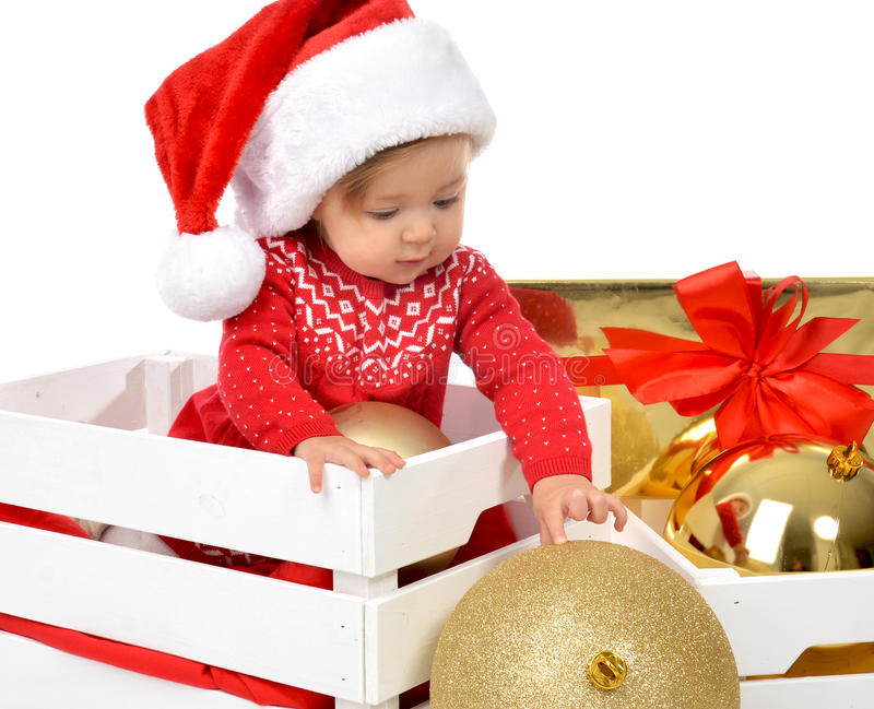 Christmas baby child in santa hat holding gold ball decoration n stock photography