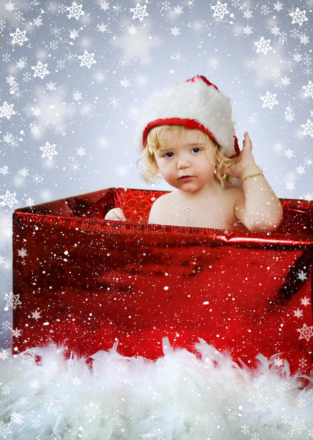 Christmas Baby Gift. Cute little baby girl sitting in a red gift box, wearing a christmas hat while snow is falling around her, with a blue background