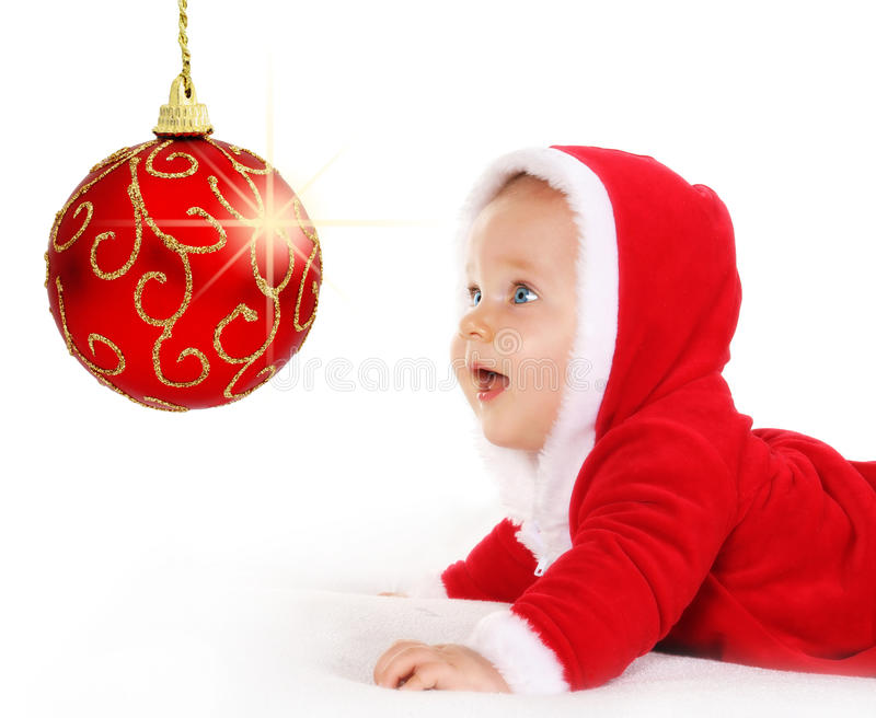 Christmas baby looking at a sparkling red ball. Cute happy baby in red Christmas clothes looking at sparkling red bauble decoration isolated on white royalty free stock photography