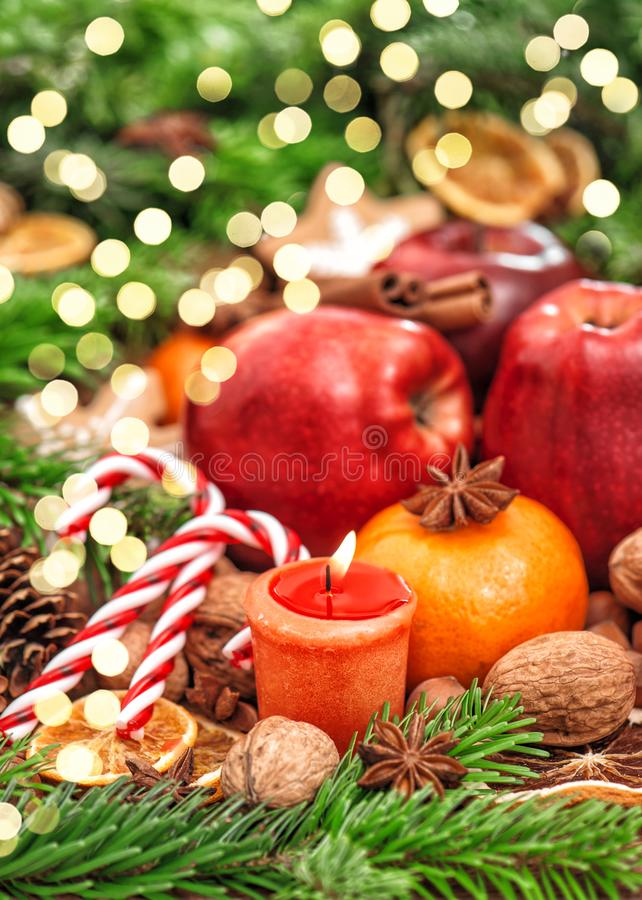 Christmas backdround Fruits spices andles golden lights. Christmas holidays backdround. Fruits, nuts, spices, candles, golden lights apple stock photo