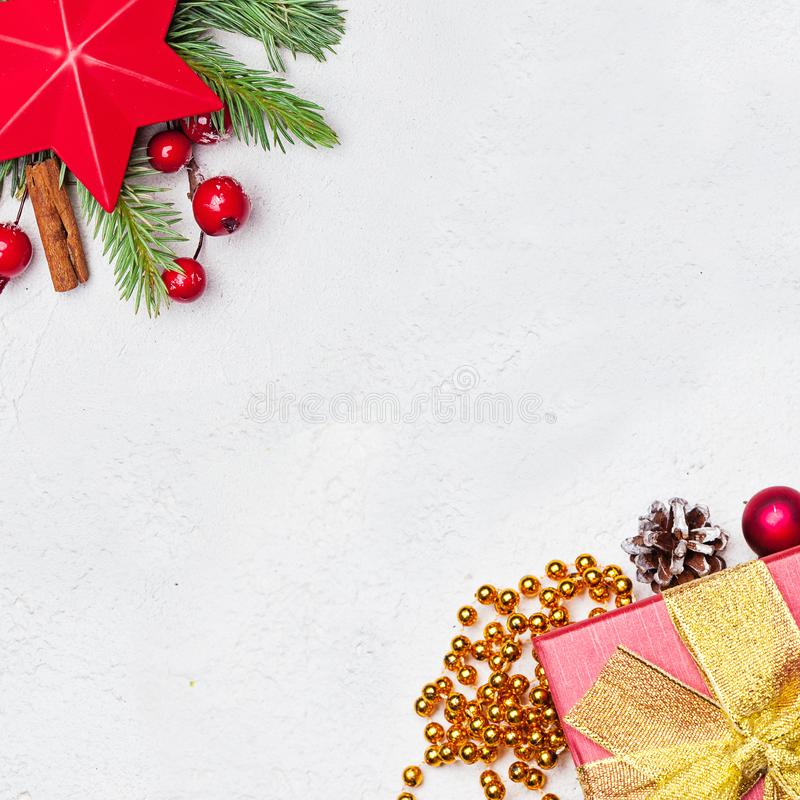 Christmas backgound. Red star, gift, green Xmas fir branch, red holly berries and baubles on white stucco plaster texture. Christmas composition, top view flat stock photography