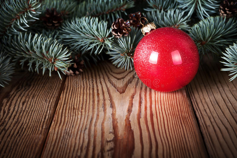Christmas Background. Red christmas ball on wooden background with branches of pine wood. Copy space royalty free stock photography