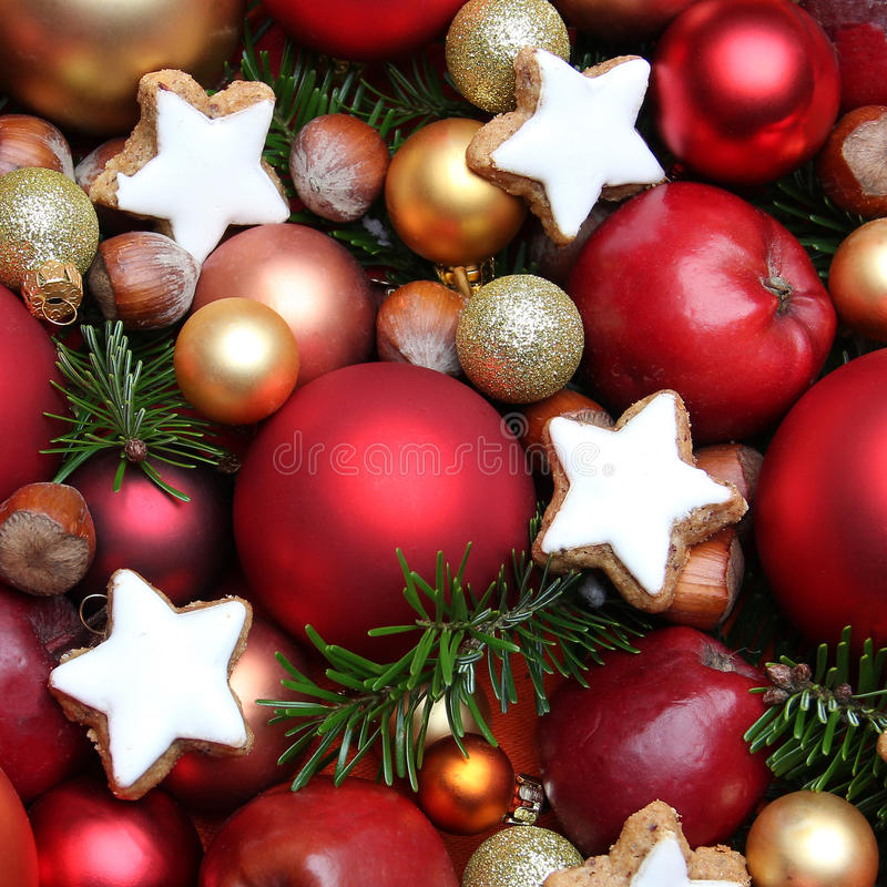 Christmas background with apples, cookies, nuts and baubles. In red and gold stock images