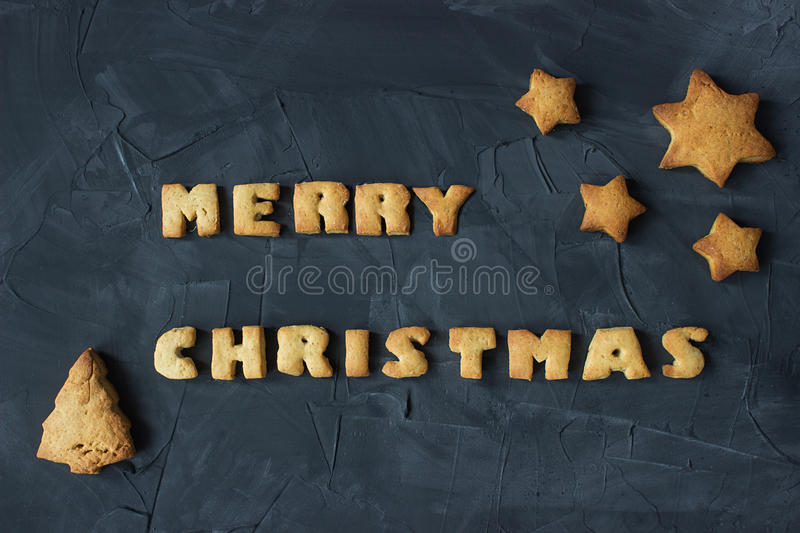 Christmas background with baked gingerbread stars, christmas tree and words merry christmas. creative idea. Christmas background with baked gingerbread stars stock photography