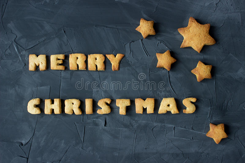 Christmas background with baked gingerbread stars and words merry christmas. creative idea. Christmas background with baked gingerbread stars and words merry royalty free stock photos