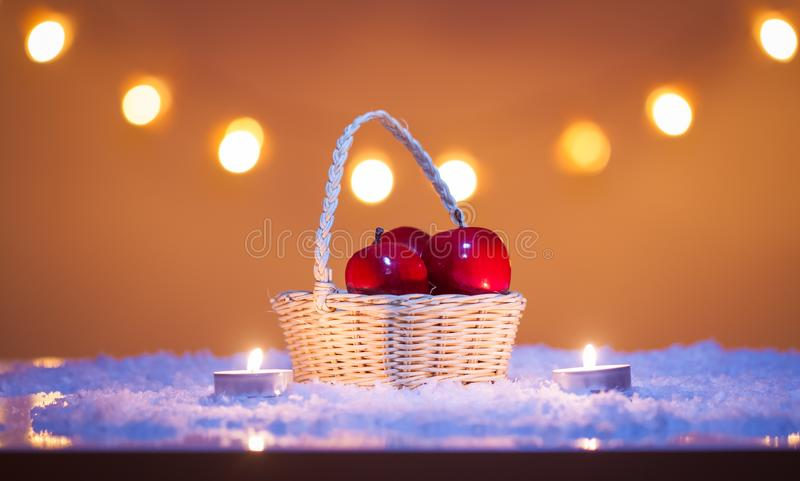 Christmas background with basket with red apples, candles, snow and bokeh lights stock photos