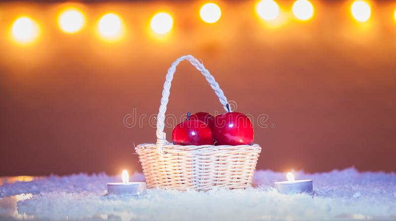 Christmas background with basket with red apples and candles, snow, bokeh lights stock photo