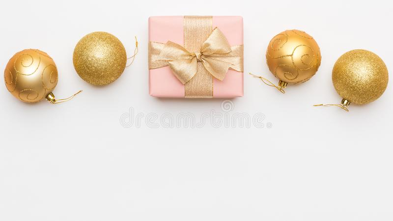 Christmas background. Beautiful pink and gold christmas gift and ornament baubles isolated on white background. Wrapped xmas box stock image
