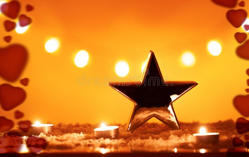 Christmas background with big silver metallic star and candles on snow, bokeh lights, orange yellow background and red hearts stock image
