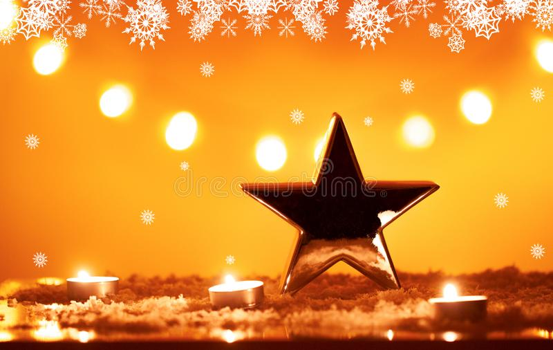 Christmas background with big silver metallic star and candles on snow, bokeh lights, orange yellow snowing background stock photos