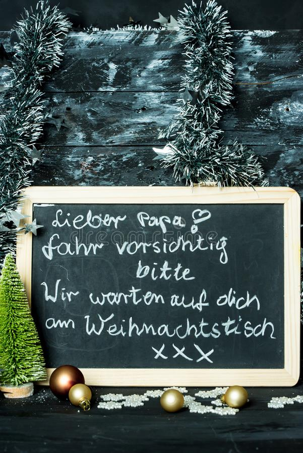 On a Christmas background a blackboard with a message from child to father: Drive carefully, we are waiting for you stock photo
