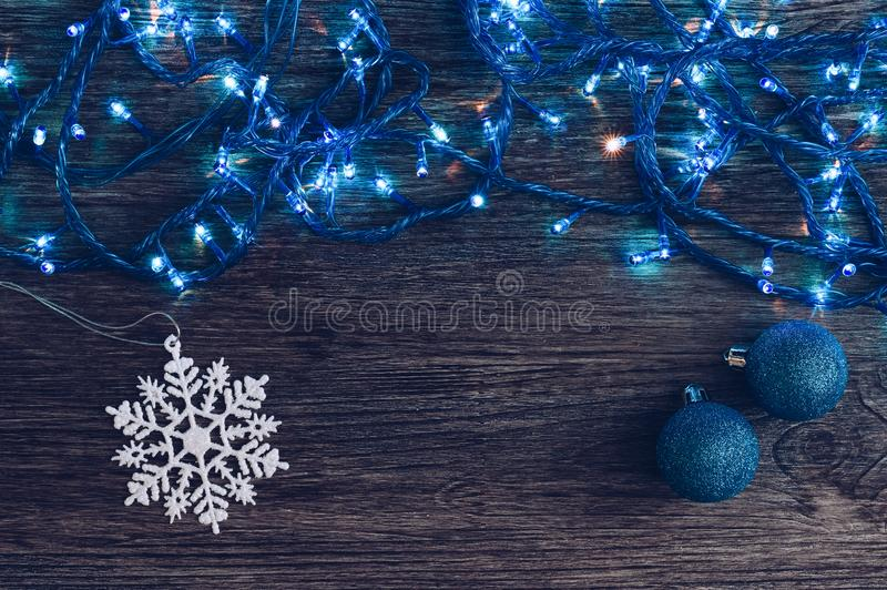 Christmas background with blue garland and lights. Christmas balls and snowflake on wooden background. Christmas background with blue garland and lights royalty free stock image
