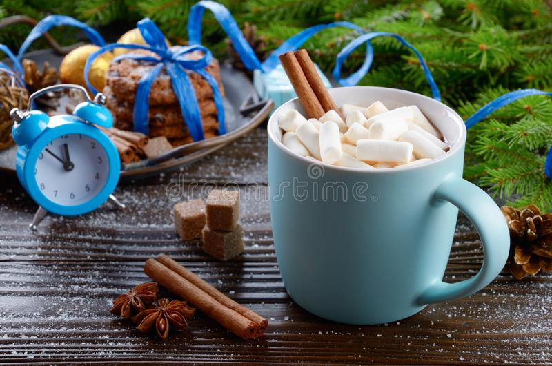 Christmas background of blue hot chocolate mug with marshmallows, spruce branch alarm clock and tray with gingerbread cookies on. Wooden table stock photography
