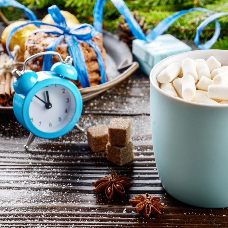 Christmas background of blue hot chocolate mug with marshmallows, spruce branch alarm clock and tray with gingerbread cookies on. Wooden table stock photo