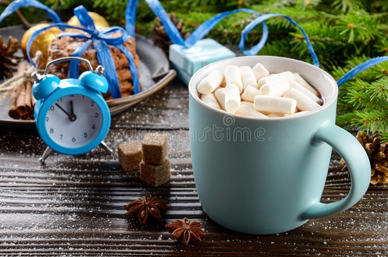 Christmas background of blue hot chocolate mug with marshmallows, spruce branch alarm clock and tray with gingerbread cookies on. Wooden table royalty free stock photography