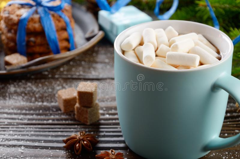 Christmas background of blue hot chocolate mug with marshmallows, spruce branch and tray with gingerbread cookies on wooden table.  royalty free stock photography