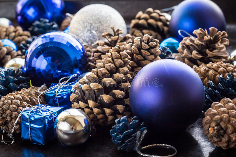 Christmas background with blue silver balls and pinecone. Christmas background with blue ornaments and snowy pinecone. Christmas party decoration with shiny stock images
