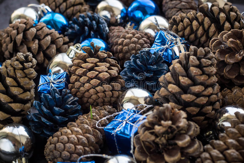 Christmas background with blue silver balls and pinecone. Christmas background with blue ornaments and snowy pinecone. Christmas party decoration with shiny stock photos