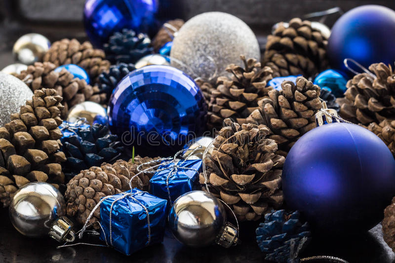Christmas background with blue silver balls and pinecone. Christmas background with blue ornaments and snowy pinecone. Christmas party decoration with shiny royalty free stock photos