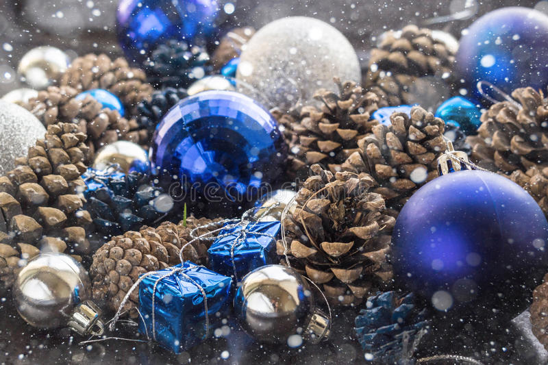 Christmas background with blue silver balls and pinecone. Christmas background with blue ornaments and snowy pinecone. Christmas party decoration with shiny royalty free stock images