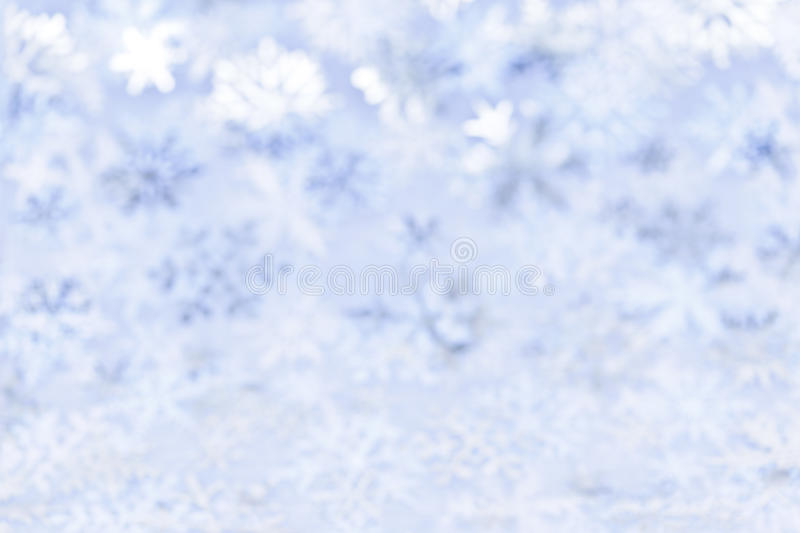 Christmas background with blue snowflakes. Blue abstract blurred Christmas background with snowflakes