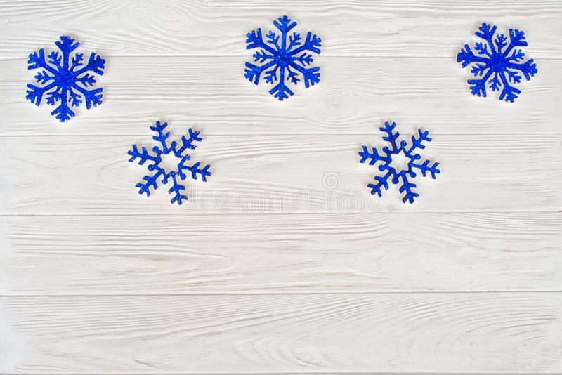 Christmas background.Blue snowflakes on a white wooden background.Top view.New Year holidays concept. royalty free stock photography