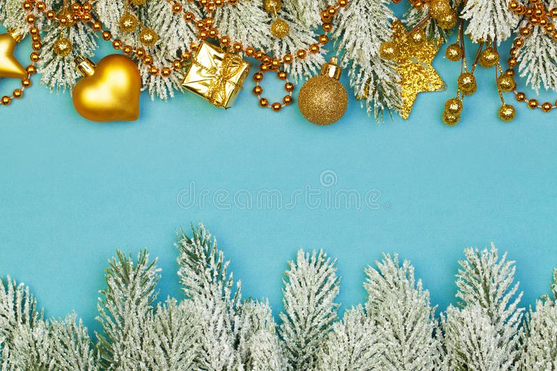 Christmas background border. Colorful Gold Xmas composition with garland, gifts and green Xmas tree branch on blue background.  royalty free stock photography