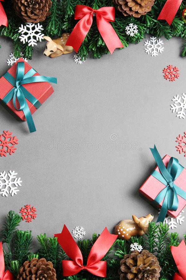 Christmas background with border made fir branches, Pine cones, Red bows, Deers, Gift boxes and white snowflakes. Top view. stock photo