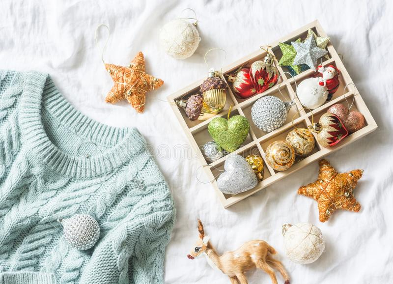 Christmas background. Box of vintage christmas decorations and blue knitted sweater on the bed, view from above. Christmas cozy mo royalty free stock photo